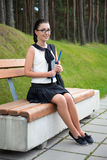 Attractive school girl or student sitting on bench in park Royalty Free Stock Images