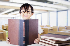 Attractive schoolgirl reading textbooks in class Royalty Free Stock Photos