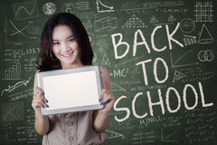 Attractive schoolgirl with tablet in class Royalty Free Stock Photography