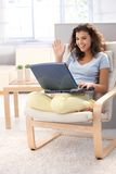 Attractive schoolgirl using laptop at home smiling Stock Photo