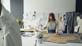 Attractive seamstress is measuring clothing paper templates lying on studio table with measure-tape. Woman is calm and. Concentrated on work in light tailor`s stock video footage