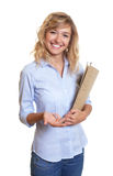 Attractive secretary with curly blond hair and file Stock Images