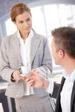 Attractive secretary handing coffee to boss. Attractive young secretary handing coffee cup to boss in bright office, smiling Royalty Free Stock Photo