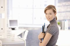Attractive secretary holding folders Stock Photography