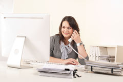 Attractive secretary on phone at office Stock Image