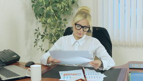 Attractive secretary scans paper and tired from stock video footage