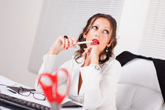 Attractive secretary. Attractive sexy secretary sitting in the office and thinking biting pencil Royalty Free Stock Image
