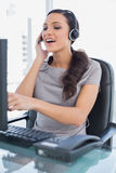 Attractive secretary wearing headset and pointing at computer sc Stock Images