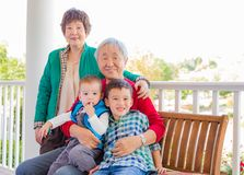 Attractive Senior Adult Chinese Couple Sitting With Their Mixed Race Grandc Royalty Free Stock Images