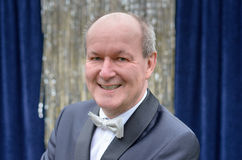 Attractive senior balding man in a bow tie. And jacket posing in front of a blue curtain with silver tinsel looking at the camera with a friendly smile royalty free stock photos