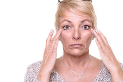 Attractive senior blond woman checking her complexion. Attractive senior blond woman with a wide-eyed expression and her glasses on her head checking her royalty free stock image