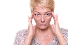 Attractive senior blond woman checking her complexion Royalty Free Stock Photos