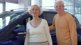 Senior couple chooses car at the dealership. Attractive senior couple choosing new car at the dealership. Aged spouses coming close to the purple crossover at Stock Images
