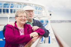 Attractive Senior Couple Enjoying The Deck of a Cruise Ship. Happy Senior Couple Enjoying The View From Deck of a Luxury Passenger Cruise Ship Stock Photography