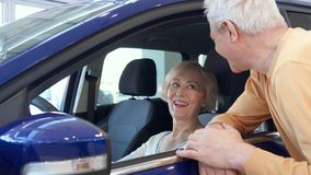 Senior couple poses with car at the dealership. Attractive senior couple posing with car at the dealership. Aged gray men looking inside the purple crossover Stock Images