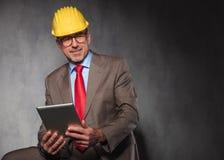 Attractive senior engineer wearing glasses and helmet Stock Photos
