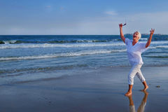Attractive senior grey haired woman dancing near sea shore royalty free stock photography
