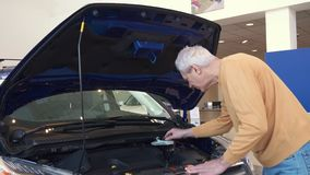 Senior man looks at engine compartment. Attractive senior man looking at the engine compartment at the dealership. Gray male customer touching mechanical parts Stock Photo