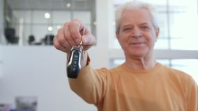 Senior man shakes car key in his hand. Attractive senior man shaking car key in his hand. Close up of caucasian male customer standing at the dealership. Aged Stock Image