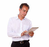 Attractive senior man using his tablet pc Stock Photos