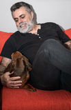 Attractive Senior with white beard Playing with dachshund dog Stock Photo