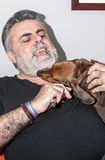 Attractive Senior with white beard Playing with dachshund dog Royalty Free Stock Image