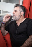 Attractive Senior with white beard smoking electronic cigarette Stock Photography