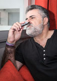 Attractive Senior with white beard smoking electronic cigarette Royalty Free Stock Photo