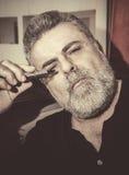 Attractive Senior with white beard smoking electronic cigarette Stock Photos