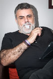 Attractive Senior with white beard smoking electronic cigarette Royalty Free Stock Photography