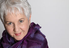 Attractive Senior Woman. Attractive, smiling, senior woman with short silver hair, wearing purple scarf stock photo