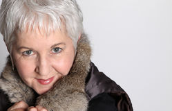 Attractive Senior Woman. Attractive, smiling, senior woman with short silver hair, wearing fur stock photos
