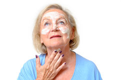 Attractive senior woman applying cream to her skin Royalty Free Stock Photography