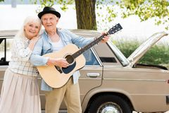 attractive senior woman embracing man playing guitar against beige stock photography