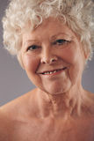 Attractive senior woman face with a sweet smile Stock Image