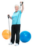 Attractive senior woman at health club. Doing exercises with a chest expander Royalty Free Stock Photography