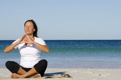 Attractive senior woman meditating at beach Stock Image