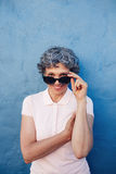 Attractive senior woman peeking over sunglasses. Vertical portrait of attractive senior woman peeking over sunglasses against blue wall. Middle aged female Royalty Free Stock Photo