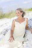 Attractive Senior Woman Sitting At Beach Stock Image