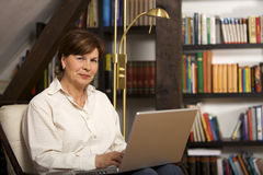 Attractive senior woman sitting with laptop. Modern senior woman sitting in front of bookshelf and working on laptop Stock Photo