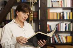 Attractive senior woman sitting and reading a book. Attractive senior woman sitting in chair at home in front of bookshelves reading a book Royalty Free Stock Photo