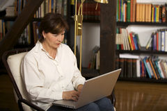 Attractive senior woman sitting and working on lap Stock Photos