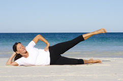 Attractive senior woman stretching at beach Stock Photos