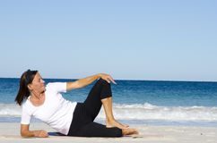 Attractive senior woman stretching at beach Stock Images
