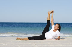 Attractive senior woman stretching at beach Royalty Free Stock Photography
