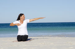 Attractive senior woman stretching at beach Royalty Free Stock Photos