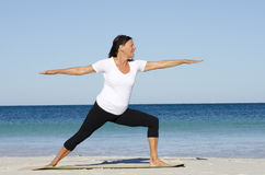 Attractive senior woman stretching at beach Royalty Free Stock Images