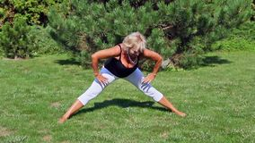Attractive senior woman is stretching exercising outdoors stock video footage