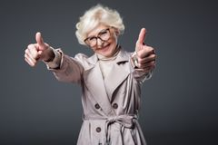 Attractive senior woman in trench coat and eyeglasses showing thumbs up,. Isolated on grey vector illustration