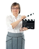 Attractive senior woman using clapperboard Stock Photos